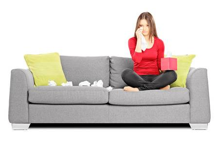 24159874-sad-young-woman-sitting-on-a-sofa-and-wiping-her-eyes-from-crying-isolated-on-white-background